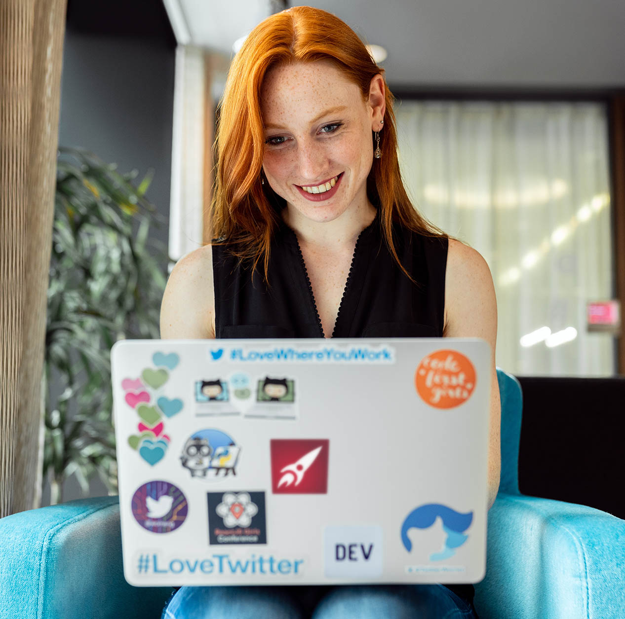 woman ginger on blue chair at laptop